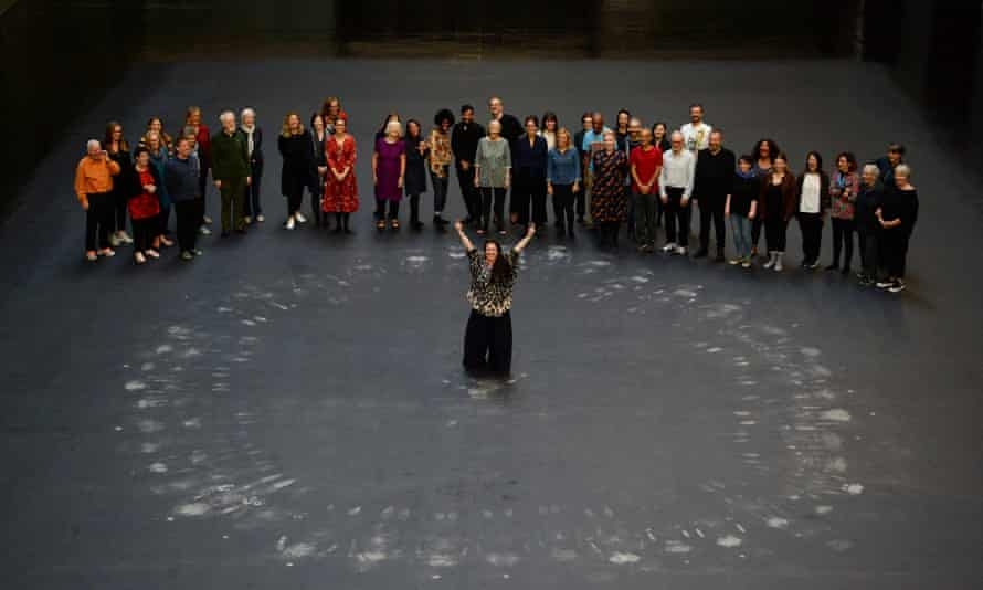 Tania Bruguera (centre) and guests stand after lying on the heat-sensitive floor during the unveiling of the installation in the Turbine Hall.