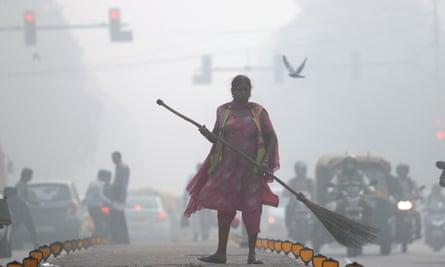 A street cleaner works in heavy smog in Delhi on November 10, 2017