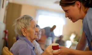 An elderly woman with a nurse in a care home.