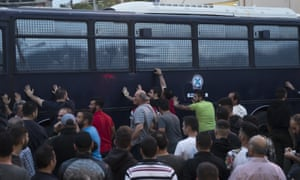 Protesters in Mytilene, Lesbos, rock a riot police bus.