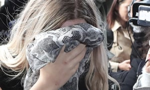 A 19-year old British woman covers her face as she arrives at Famagusta district court