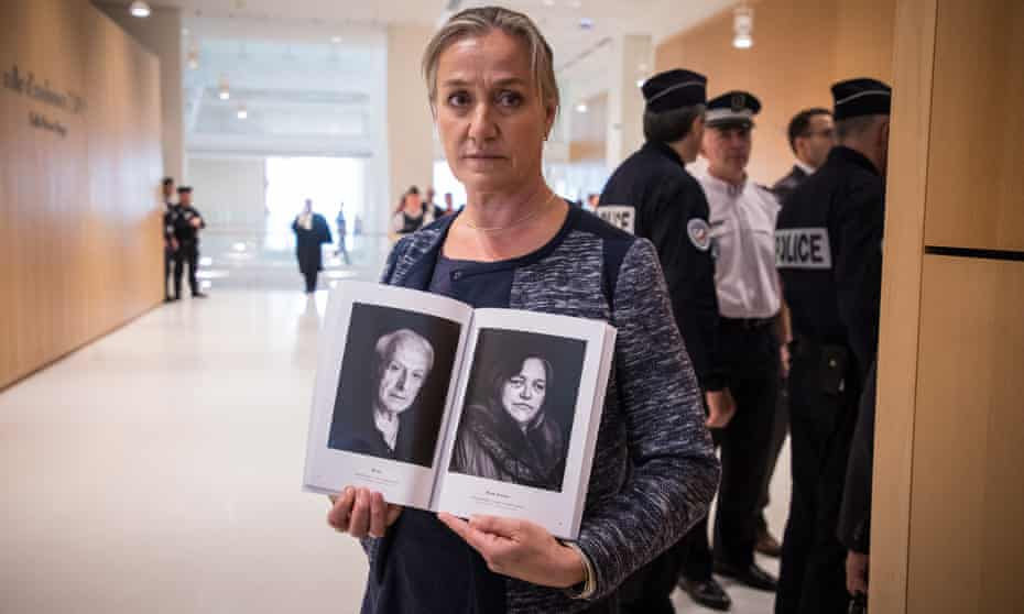 French pulmonologist Irene Frachon poses with a book of Mediator victims' portraits during the opening day of a trial at the Paris courthouse.
