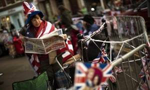 A woman reads a newspaper outside Windsor Castle before the royal wedding.