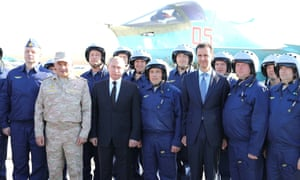 Vladimir Putin (third left) and Bashar al-Assad (third right) pose with pilots at Khmeimim airbase