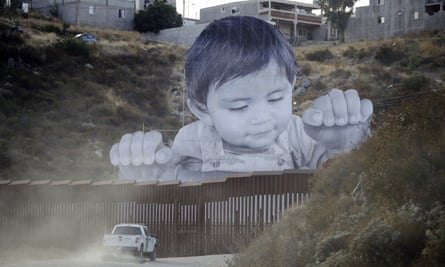A Border Patrol vehicle drives in front of a 20m mural of a boy at the US-Mexico border wall.