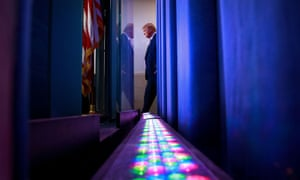 US President Donald Trump is seen from behind the backdrop of the Brady press briefing room as he arrives to lead the daily coronavirus response briefing at the White House in Washington, 1 April, 2020.