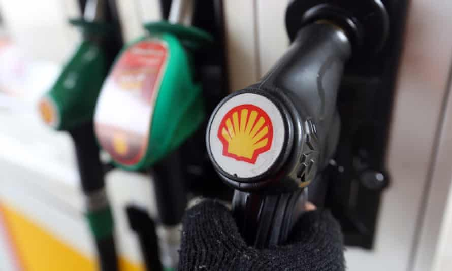 A Shell logo on a fuel pump handle on the forecourt of a petrol station