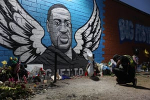 Joshua Broussard kneels in front of a memorial and mural that honors George Floyd in Houston, Texas.