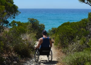 Tim Rushby-Smith in a wheelchair, seen from the back, on a sandy path looking out at the ocean