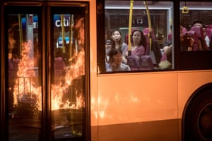 Flames from a burning barricade lit by Hong Kong pro-democracy protesters outside Mong Kok police station are reflected in the windows of a passing bus.