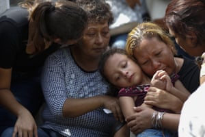 Vanessa Galindo Blas embraces one of her three children, as family members comfort each other during the burial of her husband Erick Hernández Enriquez, also known as DJ Bengala, who was killed in an attack on the White Horse nightclub in Coatzacoalcos, Mexico.