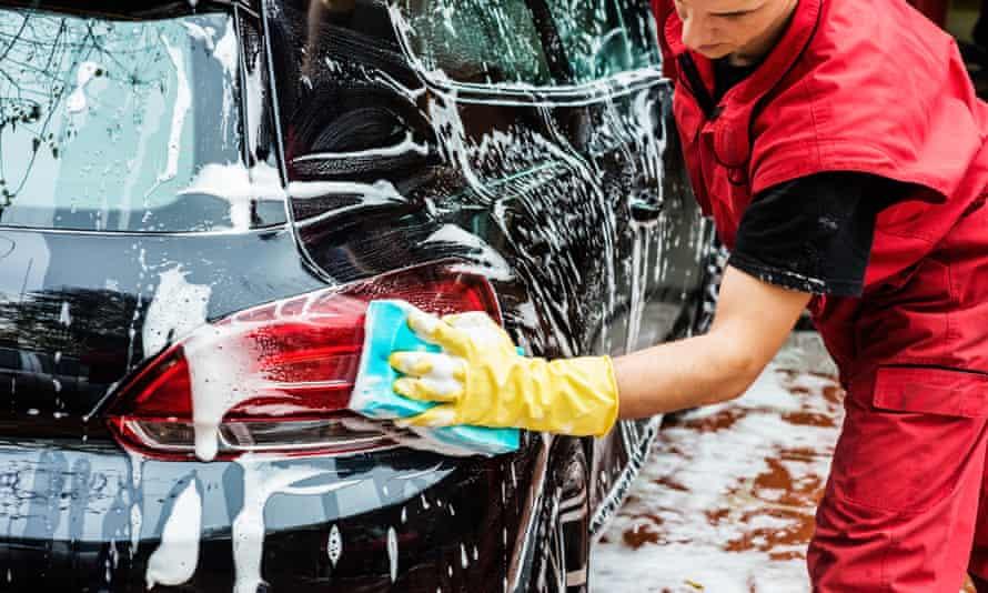 Man in red waterproof uniform at hand car wash