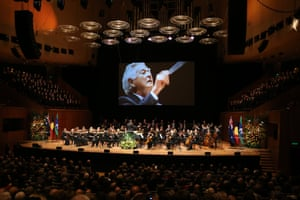 The Sydney Symphony Orchestra plays as the Sydney Philharmonia Choir sings Messiah, Hallelujah Chorus conducted on screen by the late PM, Bob Hawke.