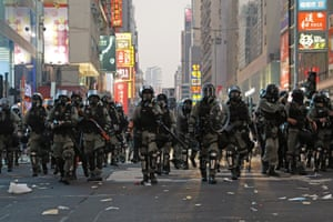Riot police advance along a street