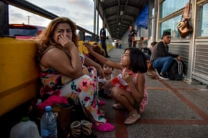 A woman from Honduras camps on the bridge with her family.