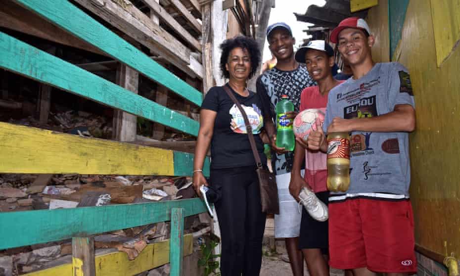 Sandra Santos, health professional at Emilio Ribas hospital, stands with three teenagers in Boi Malhado – a favela in São Paulo