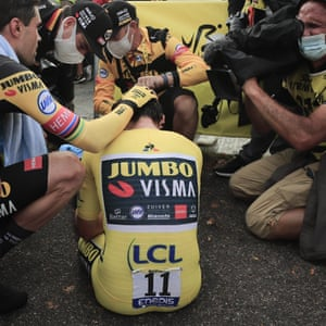 Primoz Roglic is comforted by teammates Tom Dumoulin, left, and Wout van Aert, second left, after losing the overall leader's yellow jersey in stage 20.