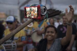 A member of a samba band uses an improvised selfie stick in Rio de Janeiro, Brazil