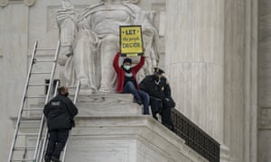 A protester opposed to the Senate's race to confirm Amy Coney Barrett is removed by police after chaining themselves to a railing and holding a sign while sitting atop the statue Contemplation of Justice, at the Supreme Court on Sunday.
