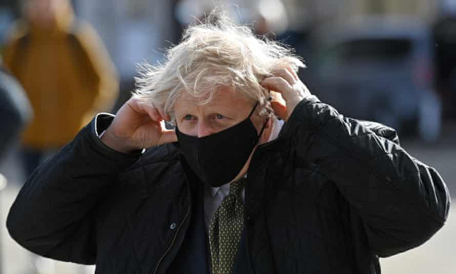 Boris Johnson outdoors in a coat, in the act of putting on a mask