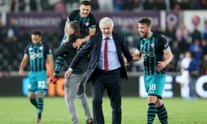 Mark Hughes celebrates with his players at full time of their win over Swansea City.