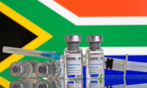 """Vials labelled """"Covid-19 Coronavirus Vaccine"""" and syringe are seen in front of displayed South Africa flag in this illustration taken, 9 February 2021."""