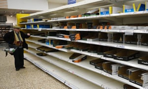 An elderly man scans the empty shelves of a north London supermarket