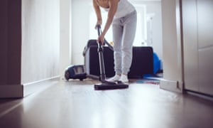 woman cleaning the floor in living room with vacuum cleaner