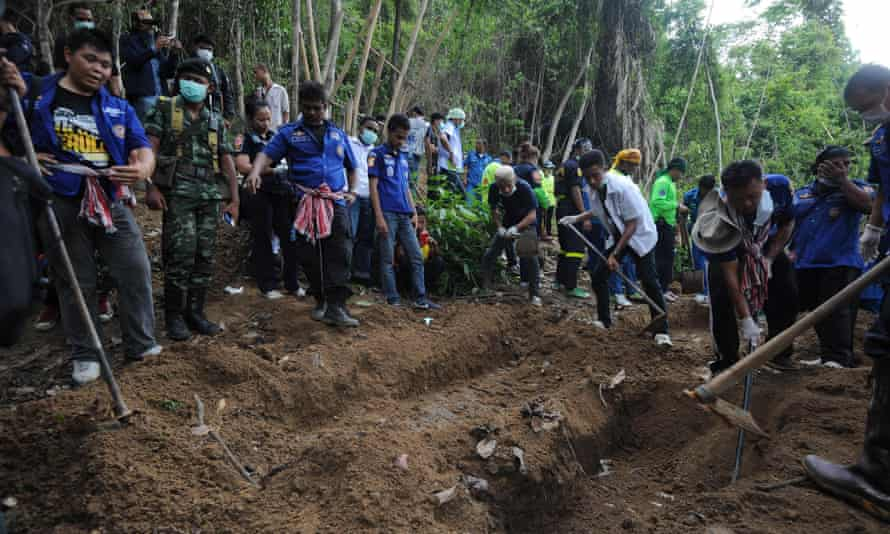Rescue workers and forensic officials dig out skeletons from shallow graves following the discovery of an abandoned jungle camp in southern Thailand in May 2015.