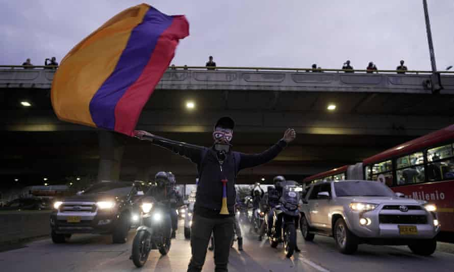 A demonstrator waves a Colombian flag among traffic in Bogotá on 4 May.