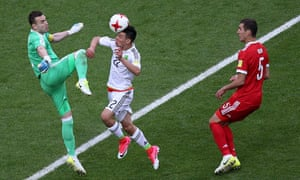 Hirving Lozano heads the ball over Russia's goalkeeper Igor Akinfeev to score Mexico's second goal.