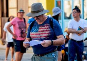 A man wearing a shirt depicting the US flag walks along a street of Havana, on December 10, 2019.