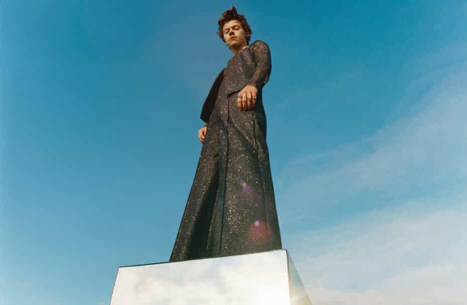 Harry Styles standing on white box, shot against blue sky background