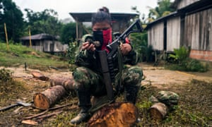 TOPSHOT-COLOMBIA-CEASEFIRE-ELNTOPSHOT - An ELN guerrilla cleans her gun in a camp on the banks of the San Juan river.