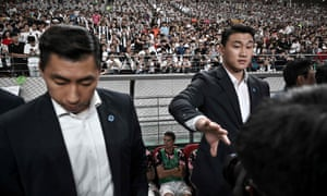 Security guards make their presence felt as Cristiano Ronaldo sits on the bench in Seoul.