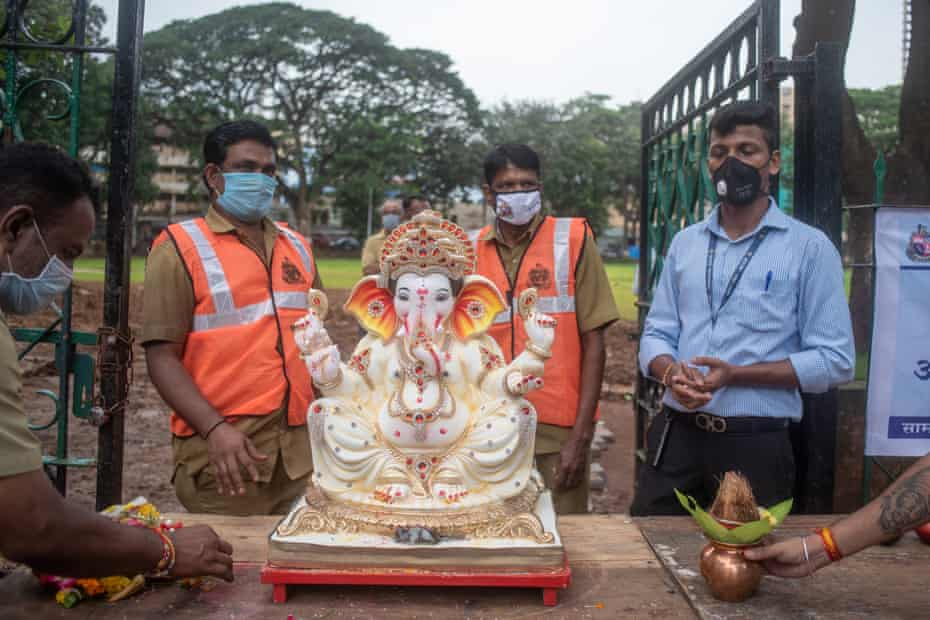 BMC workers prepare to take a statue to be immersed after its ornaments have been removed.