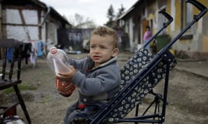 A young boy sitting in a buggy and holding a plastic bottle in front of his home in Miskolc, Hungary.