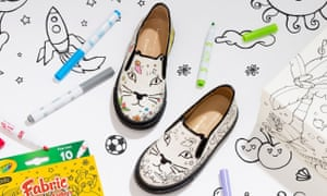 A pair of children's shoes with cat faces on in black and white with pens nearby