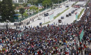 The Nepalese president's motorcade drives past people