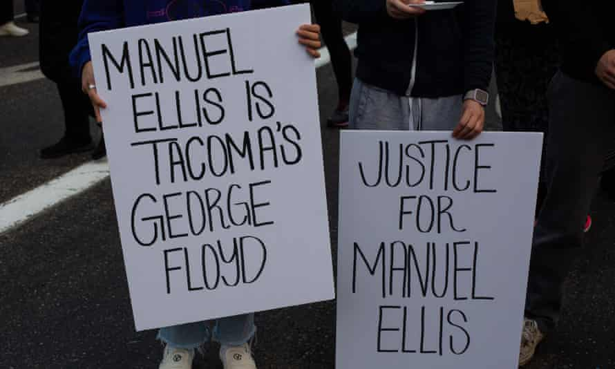 People hold signs reading 'Manual Ellis is Tacoma's George Floyd' and 'Justice for Manuel Ellis' in Tacoma, Washington last June.
