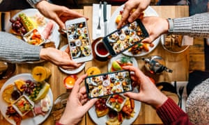 Friends taking pictures of food on the table with smartphones in a restaurant.