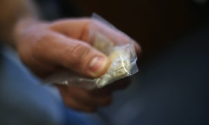 A police officer holds a bag of heroin confiscated in the US.