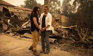 Business owner Sally Anne Wilson and her partner Christopher Lee stand in front of her destroyed shop in Cobargo