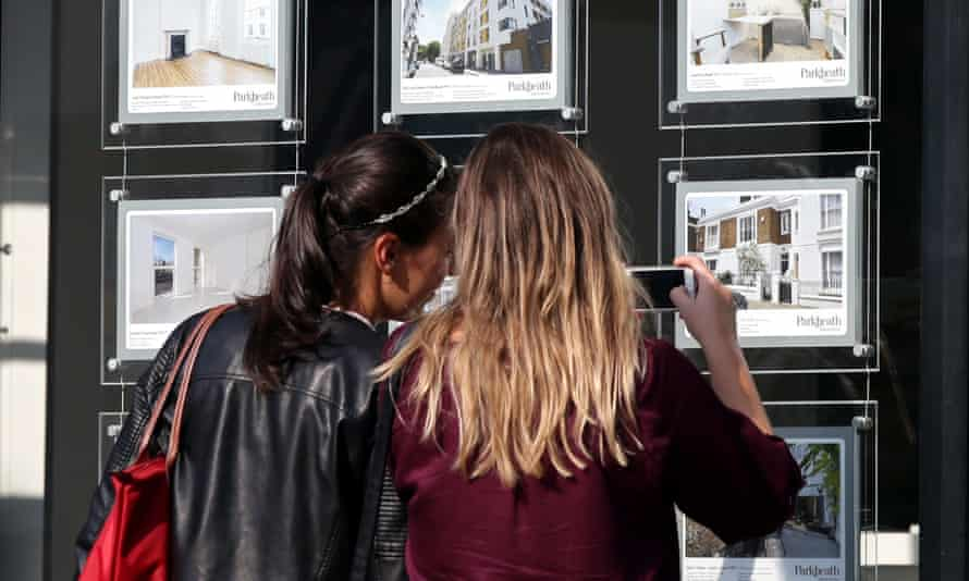 Two woman looking at houses for sale in an estate agent's window