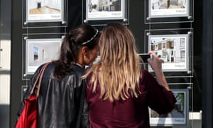 Two young women looking in an estate agents' window
