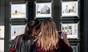 Young women looking in estate agent's window
