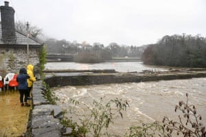 Two people watch the River Neath which is close to bursting it's banks in the village of Aberdulais, South Wales