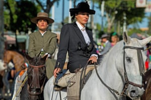 Women on horseback ride through the city side saddle