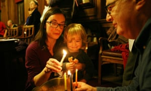 Shanon Stone and her son, Jonah Krisner, join Ben Rich in lighting candles for Hanukah at the Guildhall in York.