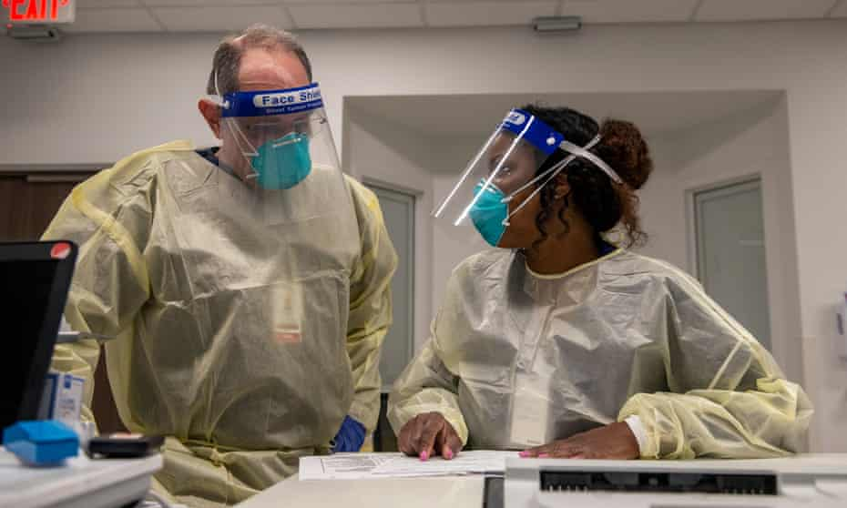Nurses Bobby Bluford (left) and Shon Hagin confer while working in the Covid isolation unit at Methodist University hospital in Memphis.